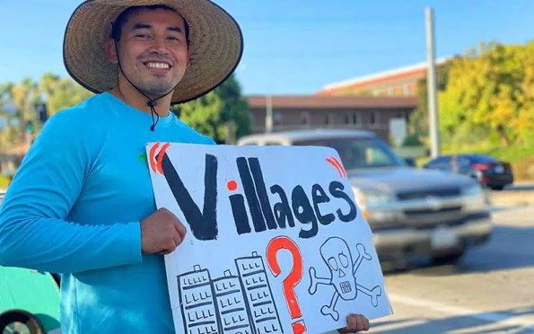 a man in a hat holding a sign quationing a development.