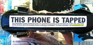 """""""This Phone is Tapped"""" is written on a public phone."""