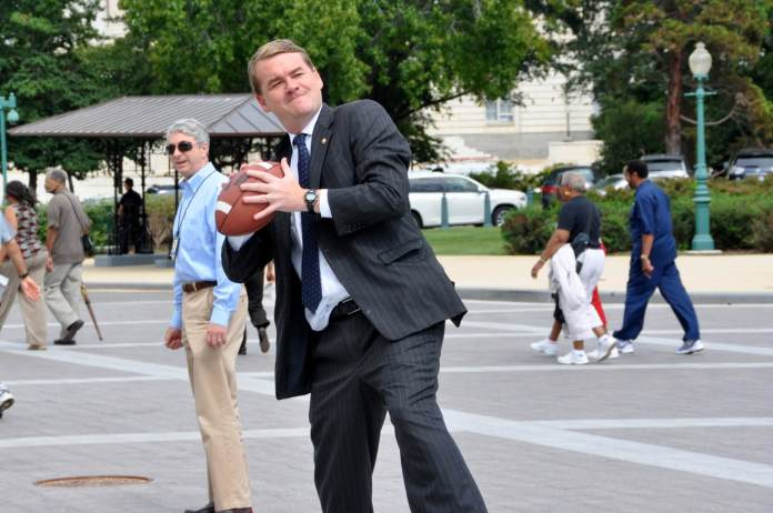 Sen. Michael Bennet drops back for a pass. (Photo by Sen. Mark Warner, D-Va., via Creative Commons: Flickr)