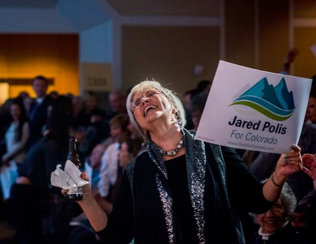 A Jared Polis supporter celebrates his gubernatorial win on Nov. 6, 2018. (Photo by Evan Semón)