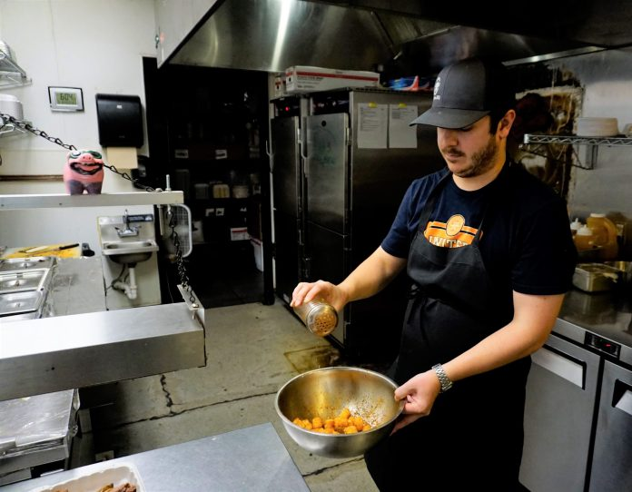 Brett Wenger prepares a take-out order at Rolling Smoke Barbecue in Centennial on Monday, shortly after Colorado Gov. Jared Polis announced a 30-day closure of all dine-in areas of bars and restaurants to combat coronavirus. (Photo by Forest Wilson)