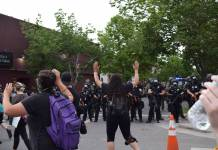 Protesters with arms raised in front of a line of police near Colfax Ave. in Denver on May 31, 2020.