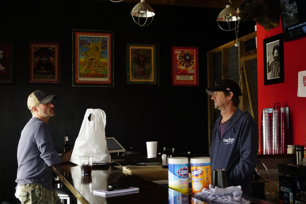 Terry Walsh (right) owner of Rolling Smoke Barbecue speaks to a take-out customer at the Centennial location on Monday. (Photo by Forest Wilson)