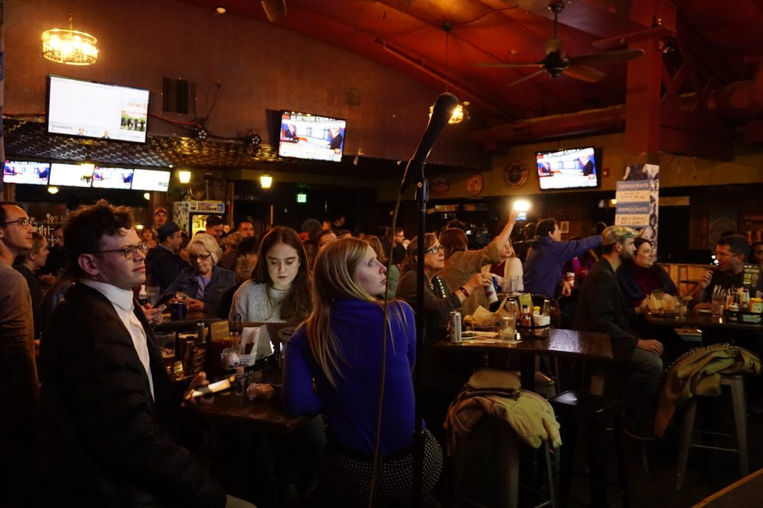 Voters watch the results of the Democratic primary at a watch party at Stoney's Bar in Denver on March 3, 2020. Bernie Sanders won with Michael Bloomberg and Joe Biden rounding out the top three. (Photo by Forest Wilson)