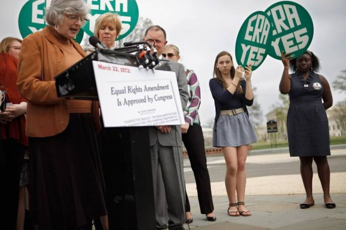 Devon Hartsough (2nd R) and Keyanna Wigglesworth (R) of the Alice Paul Institute join members of Congress and representatives of women's groups for a rally to mark the 40th anniversary of congressional passage of the Equal Rights Amendment (ERA) outside the U.S. Capitol March 22, 2012 in Washington, DC. Rep. Carolyn Maloney (D-NY) and Sen. Robert Menendez (D-NJ) introduced a new version of the Equal Rights Amendment last year and called for it to be passed again. (Photo by Chip Somodevilla/Getty Images)
