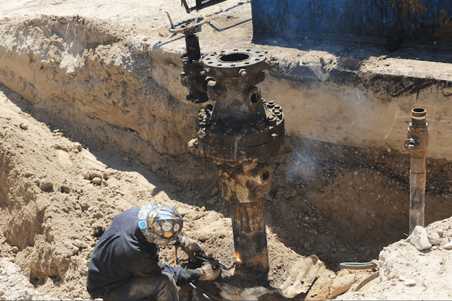 A BLM intern works to identify idle oil wells and urge operators to either put them back in production or plug them permanently. Abandoned oil and gas wells can be pathways for methane to leak into the atmosphere. (Photo courtesy of Bureau of Land Management)