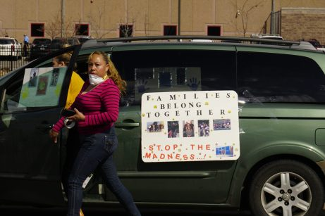 Hilda Martinez tapes posters to a car at a protest outside the ICE GEO contract facility in Aurora on April 9. (Photo by Forest Wilson)