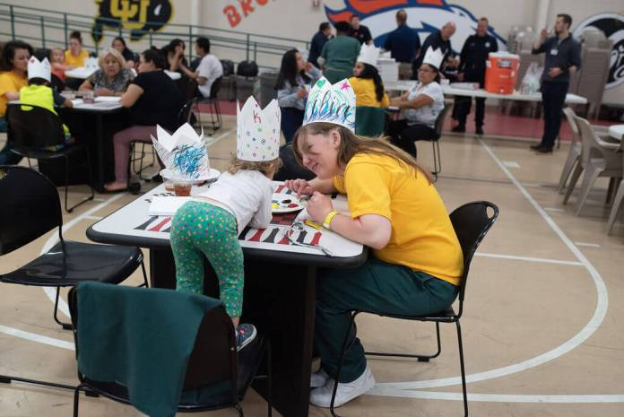 A prisoner at the Denver Women's Correctional Facility and her daughter spend time doing crafts together in the gym on a recent Saturday. (Photo by Annaleisa for the DU Prison Arts Initiative)