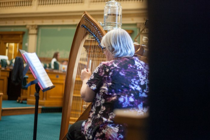 Marianne Goodland, a reporter with Colorado Politics, plays the harp on May 3, 2019, Sine Die. (Photo by John Herrick)