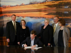 Sen. Lambert, right, looks on as Gov. Hickenlooper signs a bill to shut down CSP II.