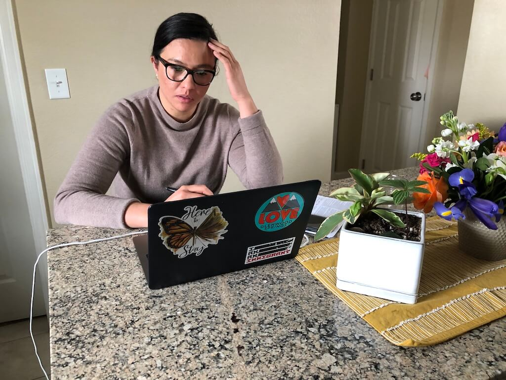 Denver resident and DACA recipient Marissa Molina works from home on a day that included phone calls on how to get COVID-19 information out to immigrants and refugees and how to help Metropolitan State University immigrant students who are now struggling. (Photo by Brad Goodall)