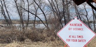 A sign reminds residents to practice social distancing on a path near the Poudre River in Fort Collins.