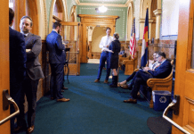 Lobbyists gather in the room immediately outside the doors to the state House chamber at the Colorado Capitol early in the 2020 legislative session. (Jesse Paul, The Colorado Sun)