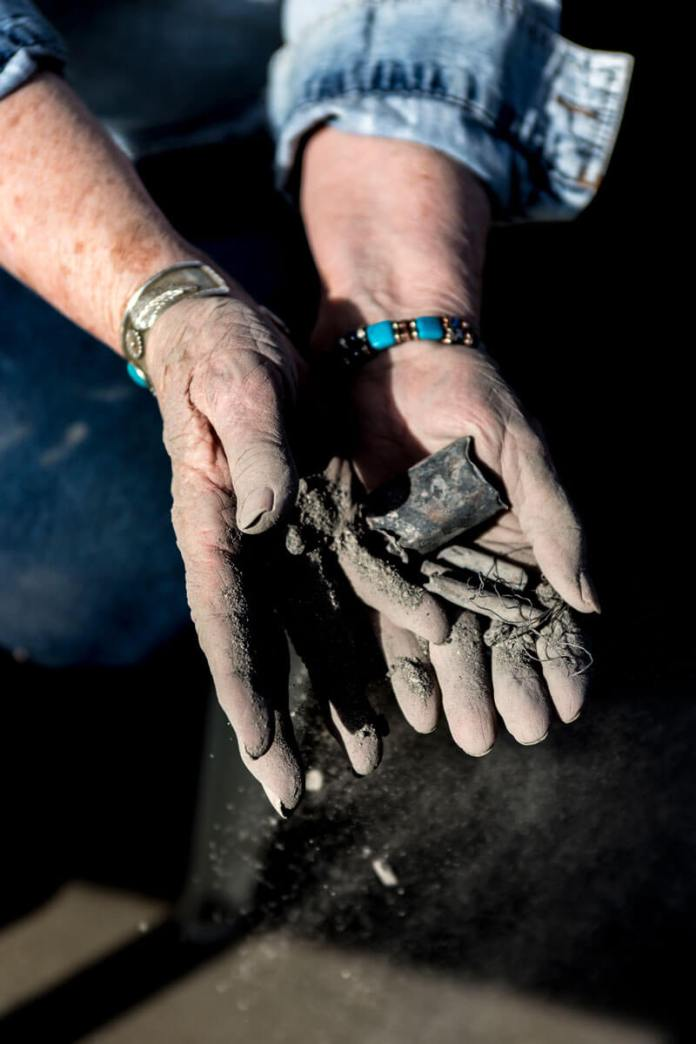 """Connie Hanson holds a handful of what Sunset Mesa Funeral Directors told her were the cremated remains of her son, Frederick """"Rick"""" Hanson. Connie Hanson believes it's burnt trash, including wires and battery casings. (Luna Anna Archey/High Country News)"""