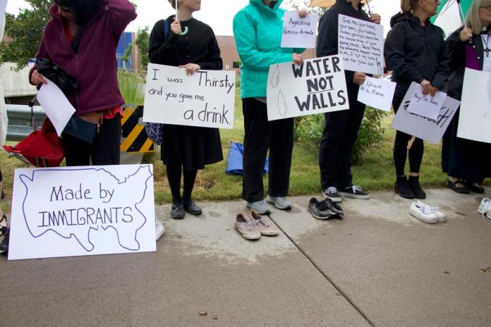 Protesters line up outside the ICE detention center for immigrants in Aurora Friday at the No More Deaths/No Más Muertes demonstration. (Photo by Grace Carson.)