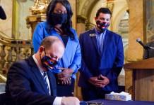 Colorado Gov. Jared Polis signs Senate Bill 217, a sweeping police accountability bill, into law at the Colorado Capitol on Friday, June 19, 2020. (Jesse Paul, The Colorado Sun)