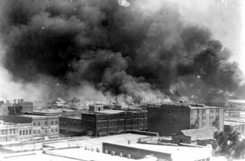 Black-and-white photo of black and brown buildings against grey sky with black smoke