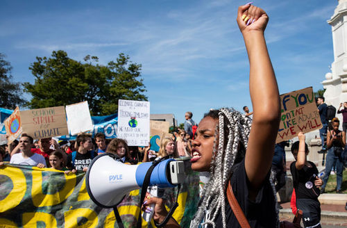 girl with a megaphone and her first in the air at climate change protest