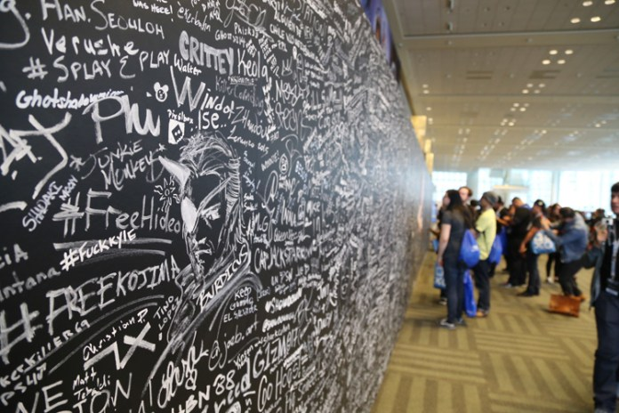 Fans write messages on Sony's commemorative wall. Filled before the first day even ended