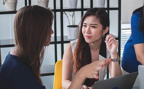 Deux femmes assises dans un bureau, discutant avec un ordinateur ouvert.