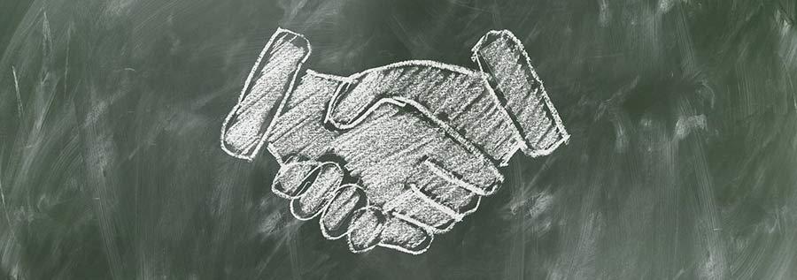 La confiance est la clé pour devenir hypnothérapeute : dessin à la craie d'une poignée de main sur un tableau noir.