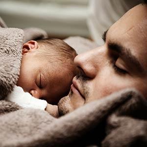 Dormir mieux grâce à l'hypnose : un nourrisson endormi dans une couverture beige, sur le torse de son papa, lui aussi endormi