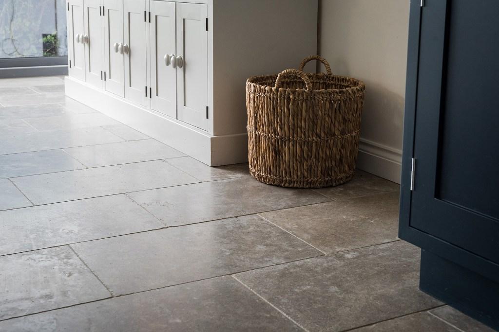 stone kitchen floor detail, with dresser and wicker log basket
