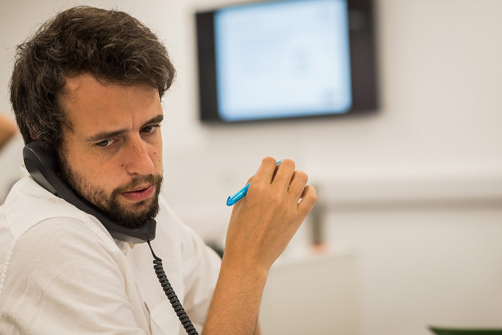 man speaking on phone in local business office
