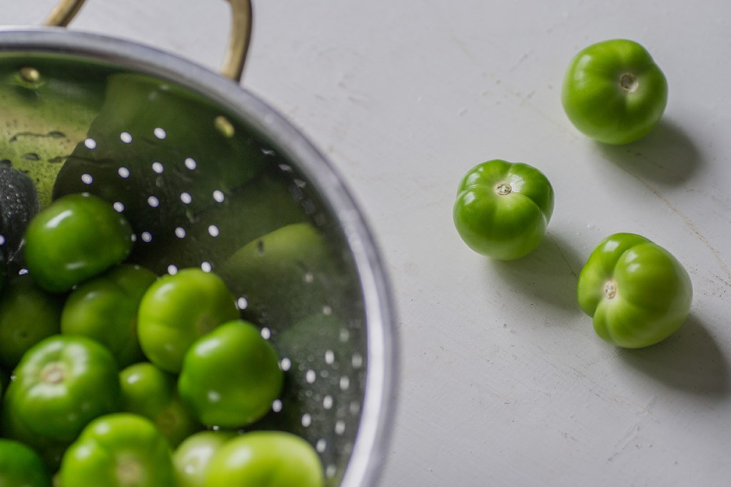 green tomatilloes on a white work surface and in a steel colander