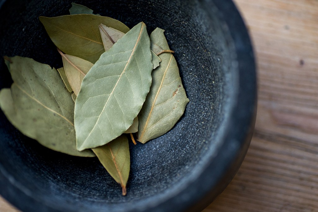 stock photo of bay leaves in stone mortar bowl