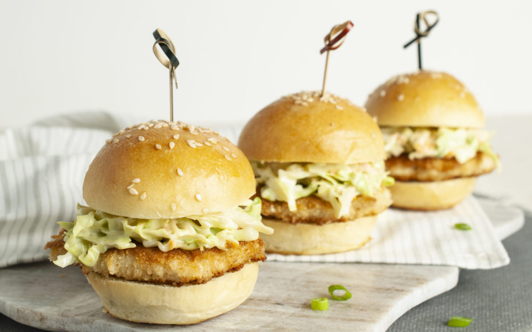 Three Crispy Chicken Sliders with Wasabi Slaw sitting in a row on a grey stripped napkin and grey marble board.