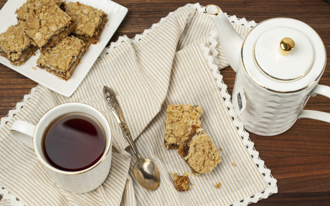 Cardamom Date Squares are scattered on a cream coloured striped napkin along with a cup of tea. Date squares are piled on a small plate to the side with a small white tea pot.