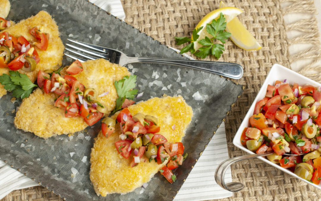 Potato Crusted Halibut with Tomato Relish ready for serving on a metal tray resting on a woven place mat and striped grey napkin.