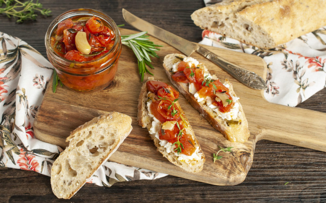 Tomato Confit in a small jar and spread onto goat cheese covered baguette slices that rest on a wooden board and floral napkin, with a knife resting to the side.