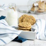 Coconut Oatmeal Cookies rest on a blue and white striped napkin that is draped through a white wooden tray. A small glass bottle of milk sits to the side and a canister of cookies lays in the background.