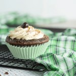 A single Irish Cream Cupcakes sits in focus in the foreground. It sits on a black cooling rack draped with a green and white checkered towel. The background is blurry.