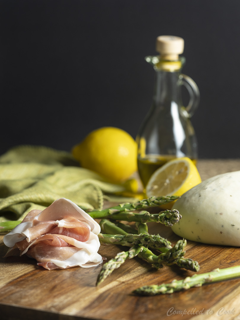 Fresh ingredients for Grilled Prosciutto and Asparagus Flatbread arranged on a wooden cutting board.
