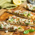 Grilled Prosciutto and Asparagus Flatbread cut into wedges on a wooden cutting board.