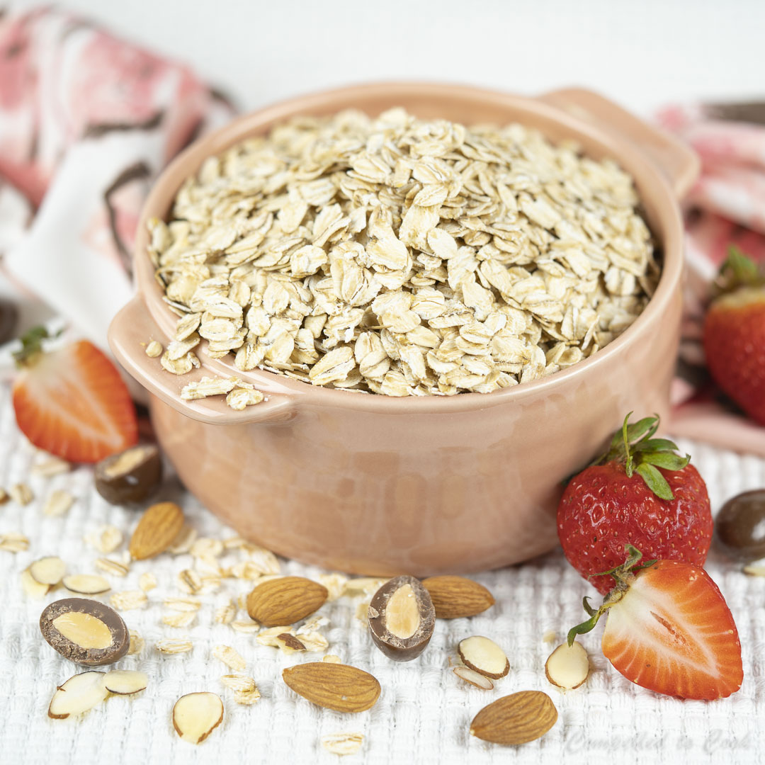 A pink bowl filled with large flake oatmeal has almonds and strawberries scattered around it in preparation for Ultimate Chocolate Almond Granola.