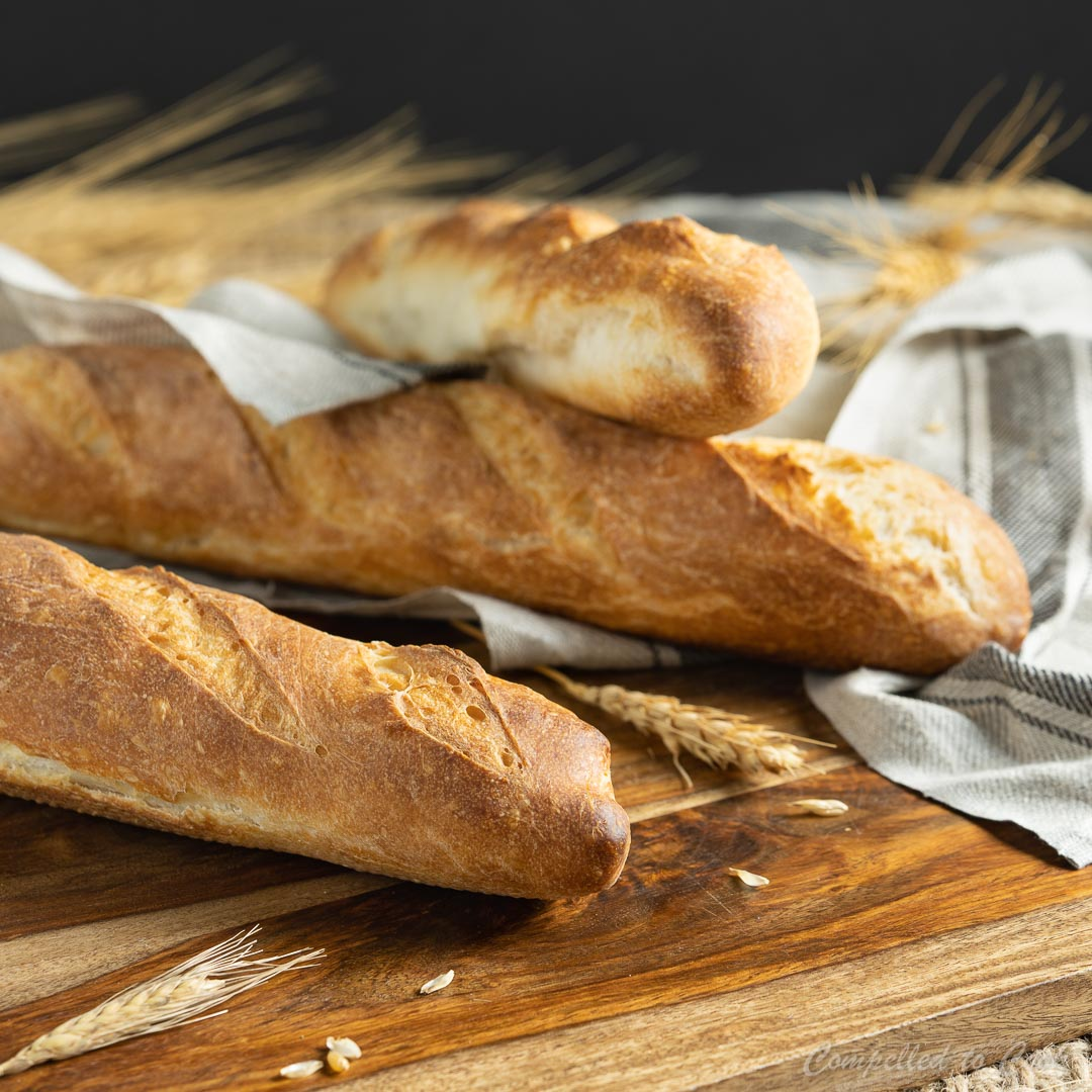 Three Easy Homemade Baguettes are baked golden and resting on a wooden board with a linen kitchen towel.