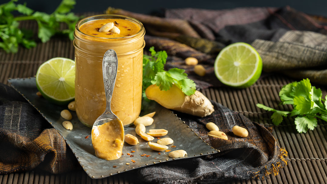 A spoon heavy with peanut sauce stands against a mason jar filled with peanut sauce.