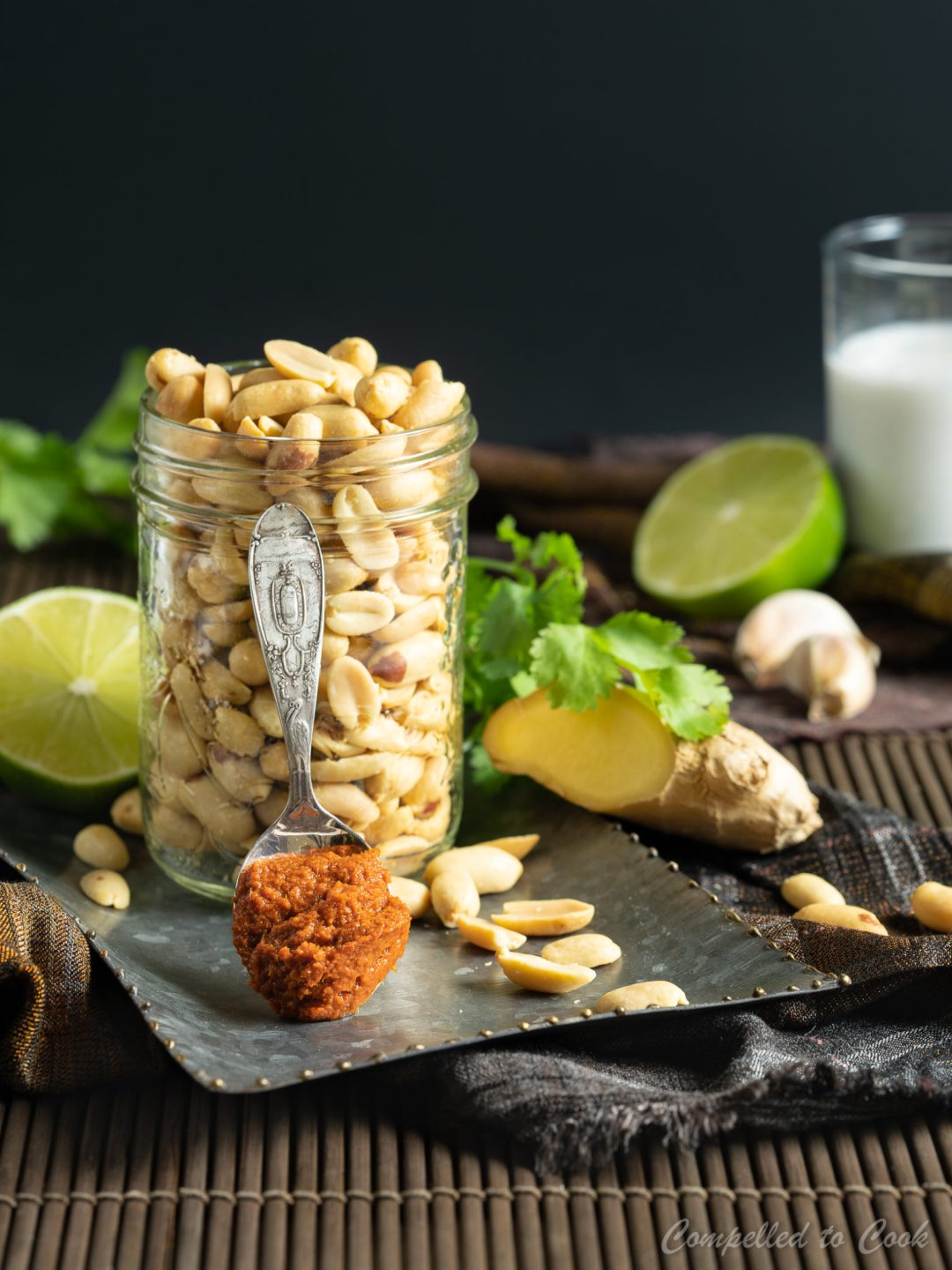 Whole peanuts fill a mason jar that is surrounded by ginger, curry paste, garlic, lime and coconut milk in preparation for Peanut Sauce.