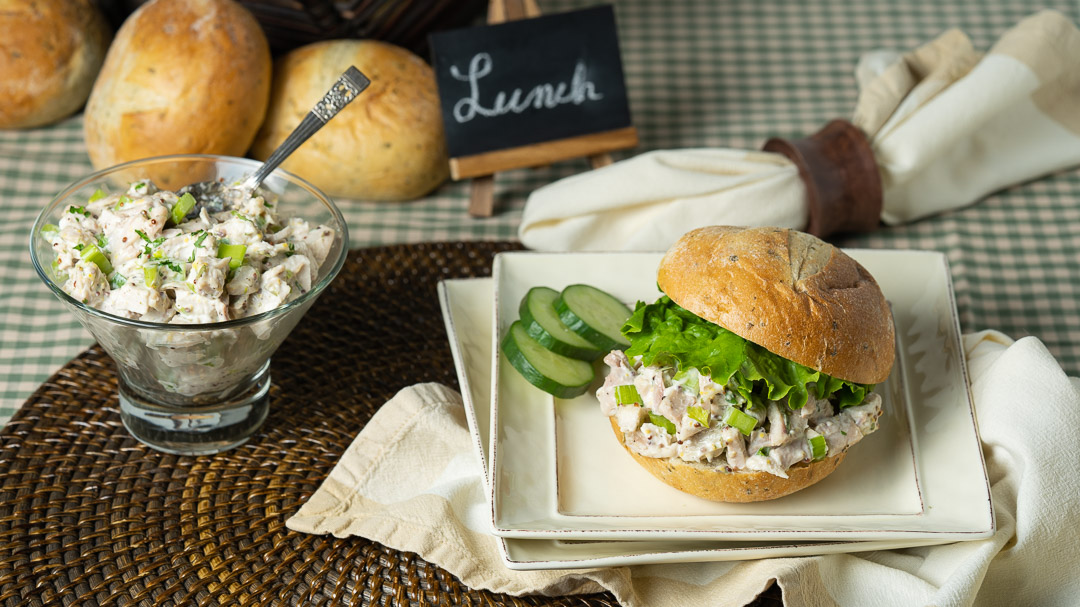 Tarragon Chicken Salad is piled high and topped with lettuce on a golden bun. The bun sits on a stack of plates garnished with cucumber slices.