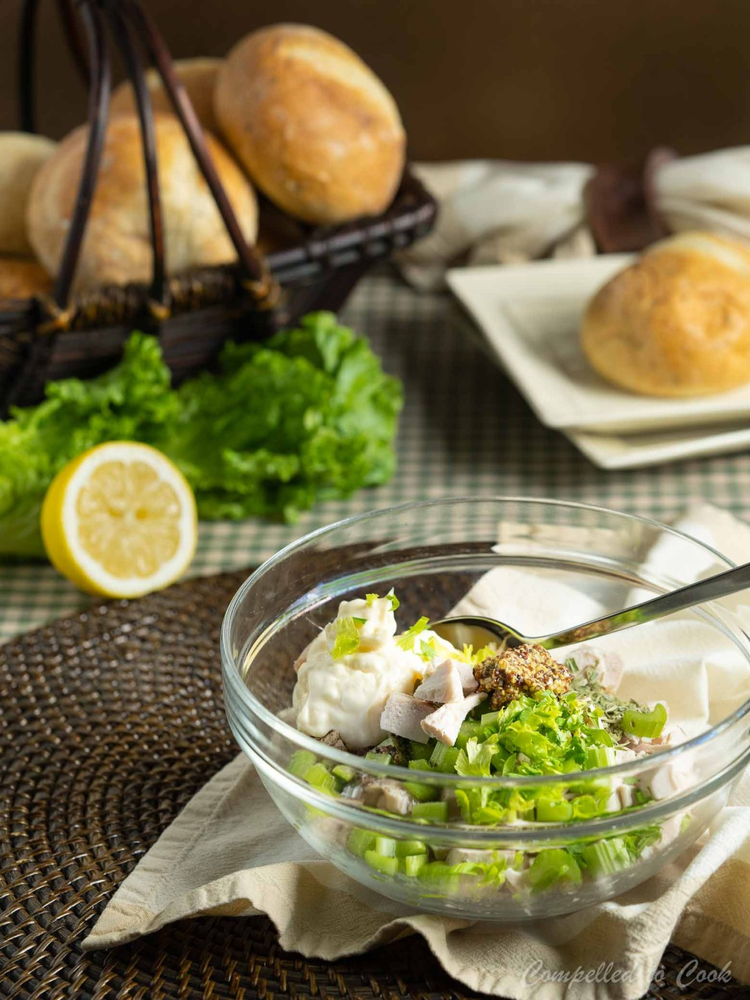 Ingredients for Tarragon Chicken Salad are measured into a glass bowl and ready to be stirred. A basket of buns sits in the background.