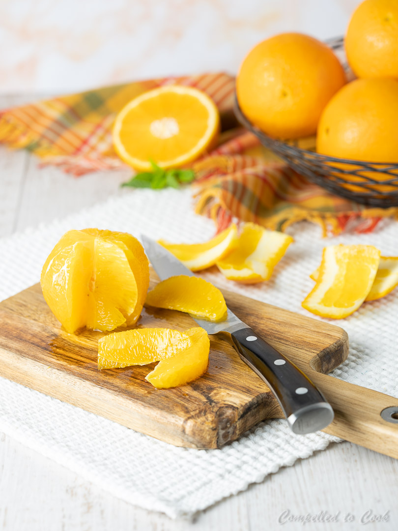 Peeled and wedged oranges on a cutting board with a basket of oranges in the background.