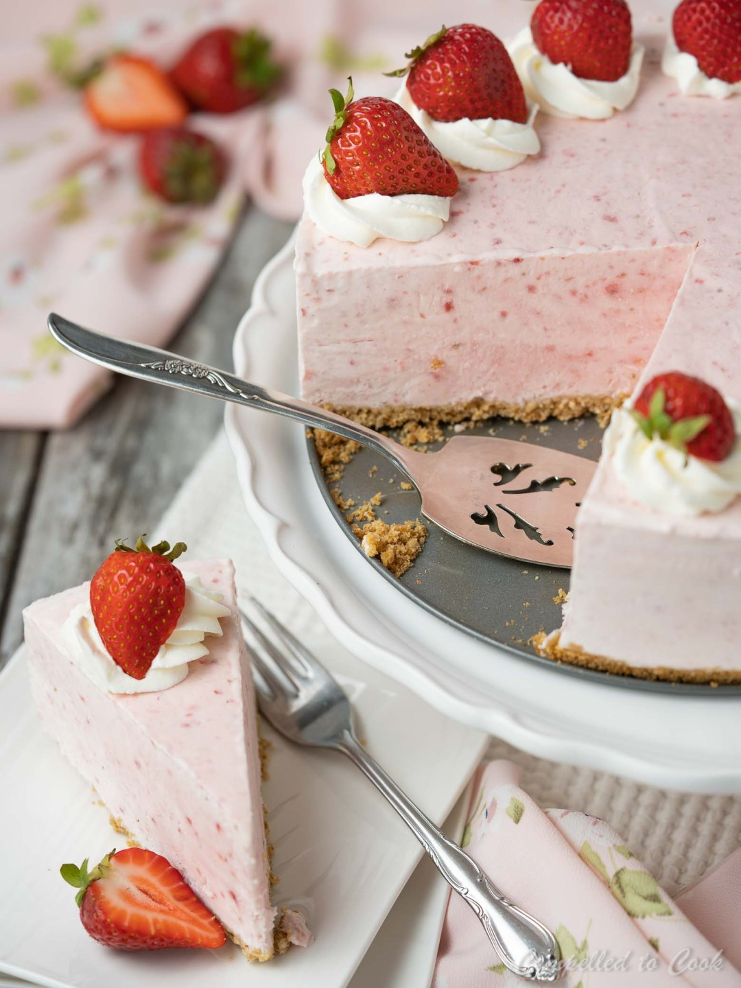 Frozen Yogurt Strawberry Cake with a large wedge cut out and resting on a serving plate.