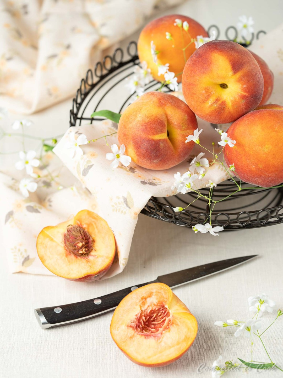 Fresh peaches stacked on a metal tray in preparation for Whole Wheat Peach Streusel Muffins.