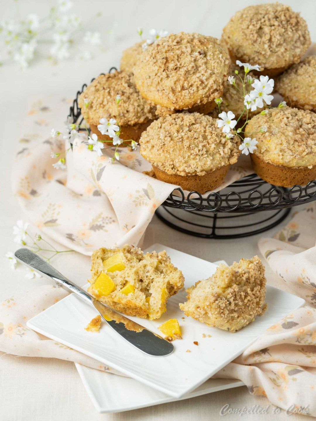 Whole Wheat Peach Streusel Muffins stacked on a metal stand with a split muffin on a plate in the foreground.