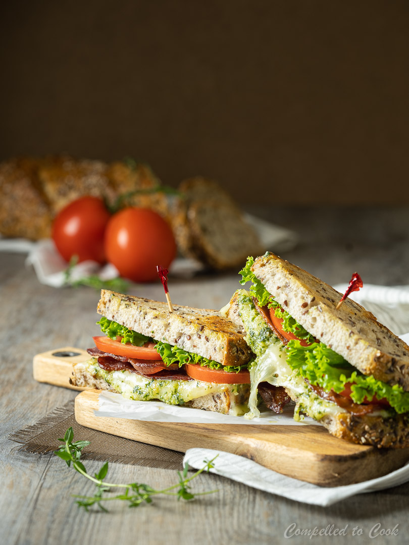 Cheesy Pesto BLT sandwich cut and stacked on a small wooden tray.