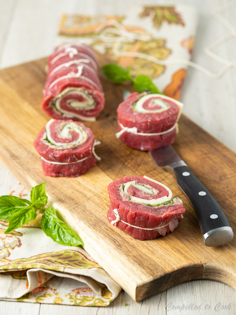 Flattened flank steak rolled and tied with basil, provolone and prosciutto and ready for grilled Beef Roulade.